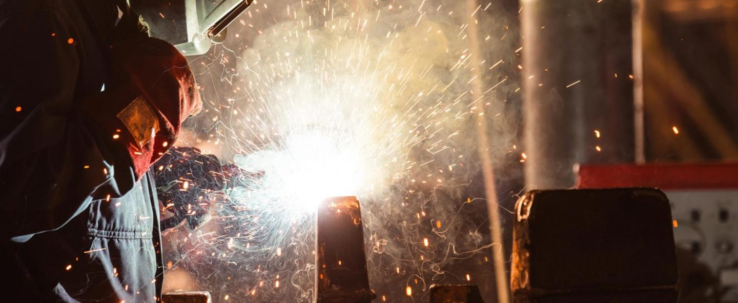 Side shot of a Universal Wolf welder wearing overalls, gloves and ventilation equipment, working on a piece of metal frame, with yellow sparks coming from welding tool