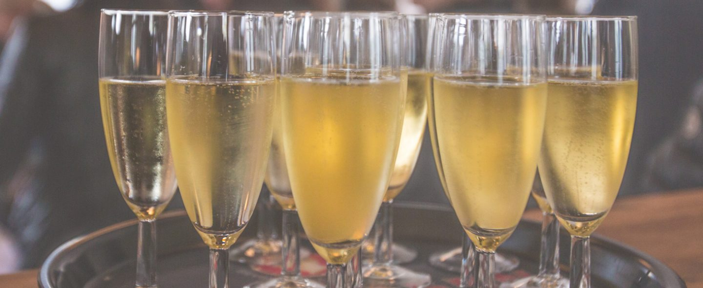 filled champagne flutes on a tray