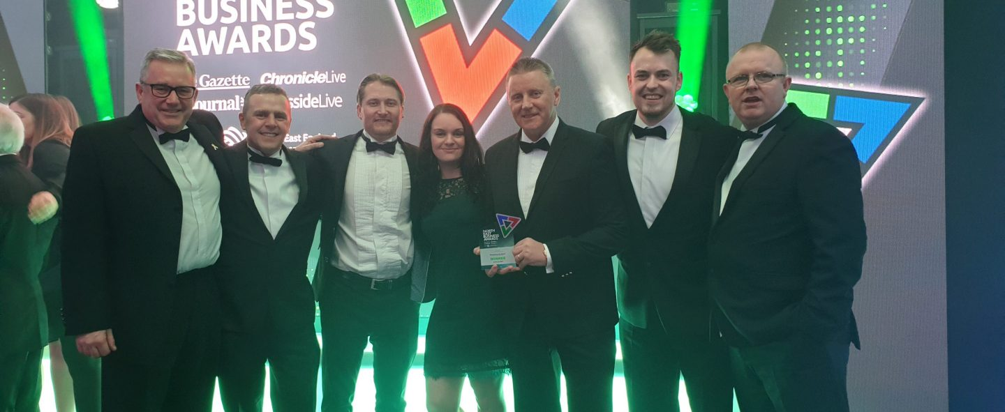 Universal Wolf employees standing on stage at the North East Business Awards 2019 regional final, holding an award