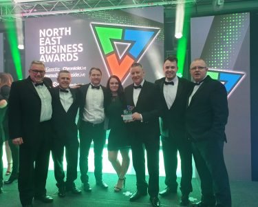 7 Universal Wolf employees standing on stage at the North East Business Awards 2019 regional final, holding an award