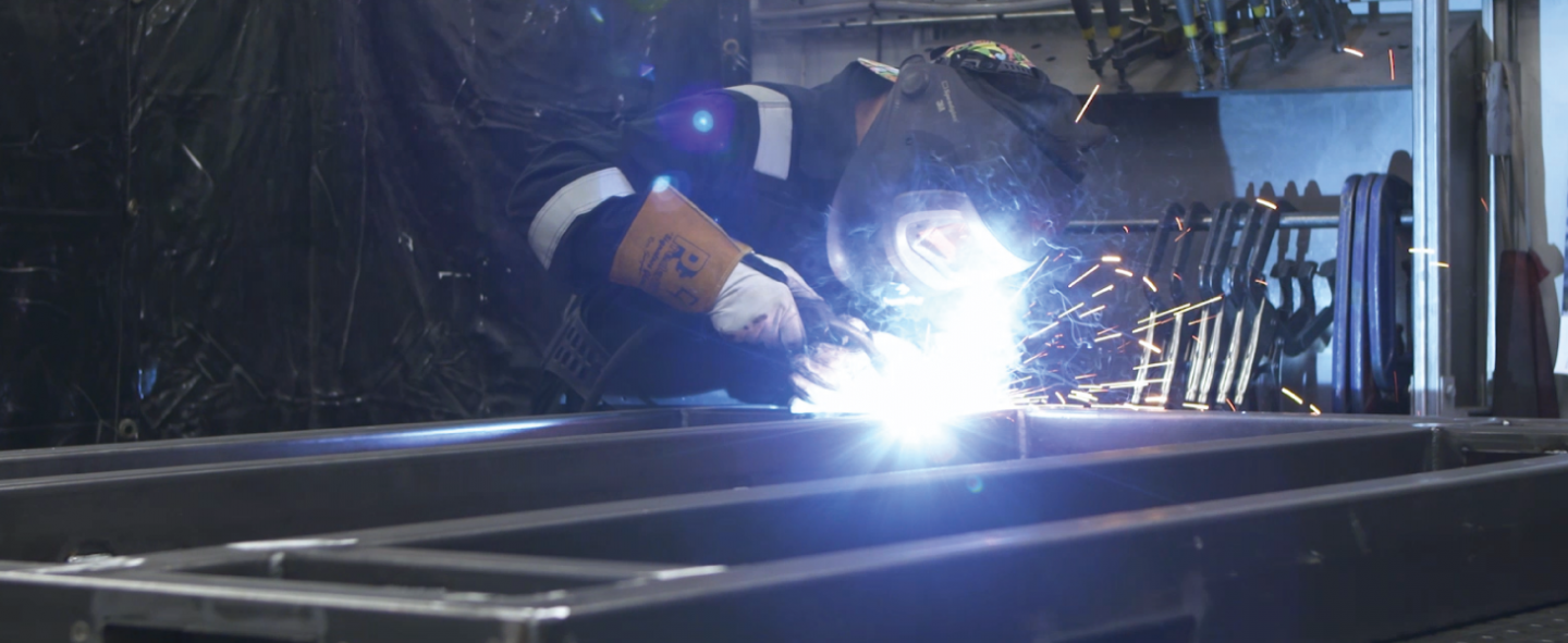 Universal Wolf welder working on a complex metal fabricated frame, wearing protective equipment