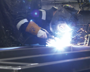 welder working on a metal fabricated frame, wearing protective equipment