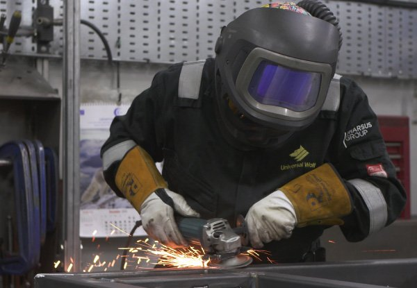 welder wearing a protective mask and ventilation equipment grinding a metal frame
