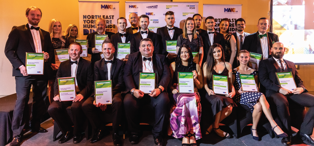 All winners at the Make UK awards for North East, Yorkshire and Humberside standing and sitting on a stage, wearing evening dress, holding their awards, with banners in the background