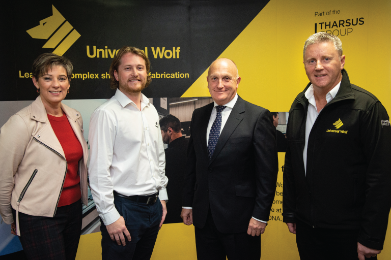 June Smith Make UK, Craig Brown Universal Wolf, Stephen Phipson Make UK and Patrick MacDonald Universal Wolf, standing looking straight to camera, in front of a black and yellow Universal Wolf promotional banner