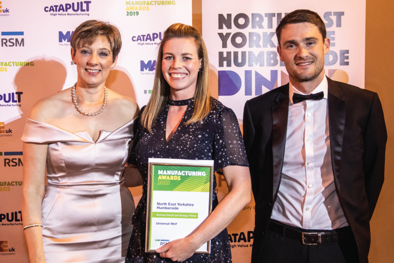Stephanie Knox of Universal Wolf standing holding their Business Growth and Strategy award, with June Smith of Make UK and a fellow award presenter, in front of Make UK promotional banners