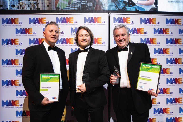 3 directors from Universal Wolf holding awards and certificates, standing in front of Make UK banner