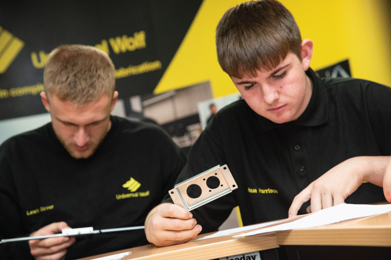 2 male apprentices looking at drawings and holding metalwork pieces