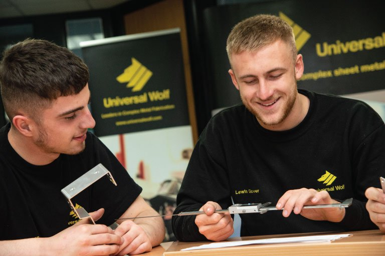 2 apprentices looking at some metalwork samples