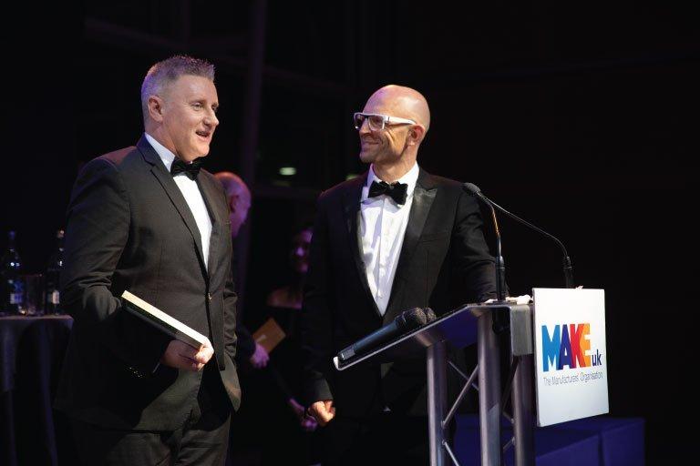 2 men on stage holding Make UK 2020 award in front of a pedestal