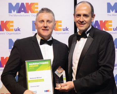 Patrick Macdonald from Universal Wolf stands with a judge in front of a Make UK-branded banner, holding an award and certificate