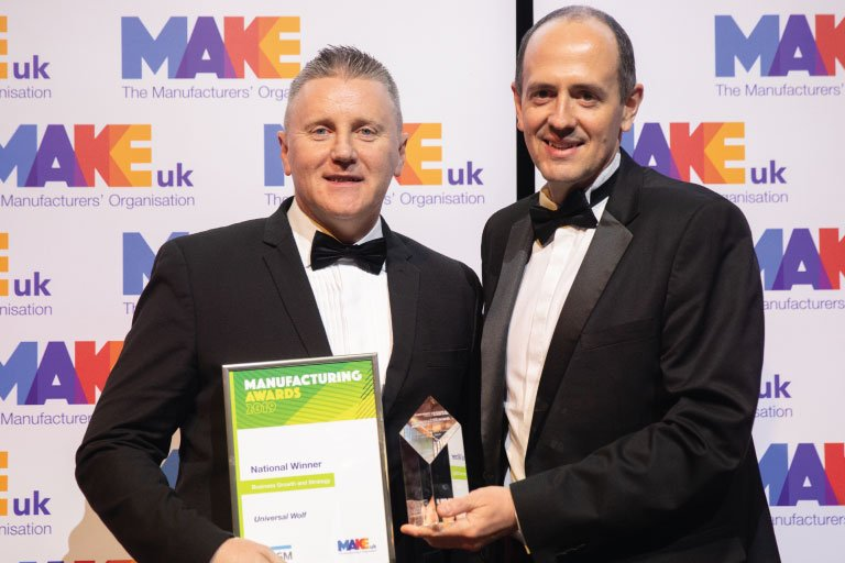 Patrick Macdonald from Universal Wolf stands with a judge at the Make UK National Awards 2020, holding an award and certificate
