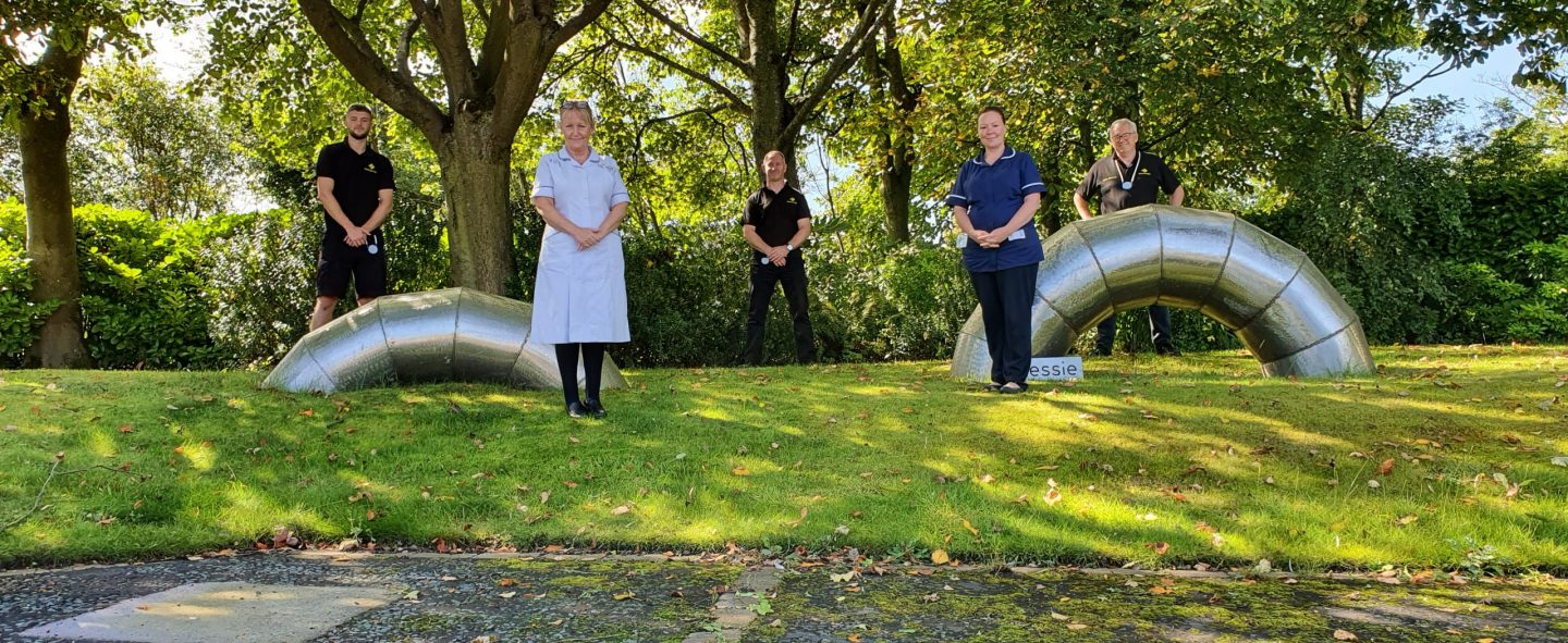 Universal Wolf and St Oswald's Hospice staff standing next to Nessie metal installation