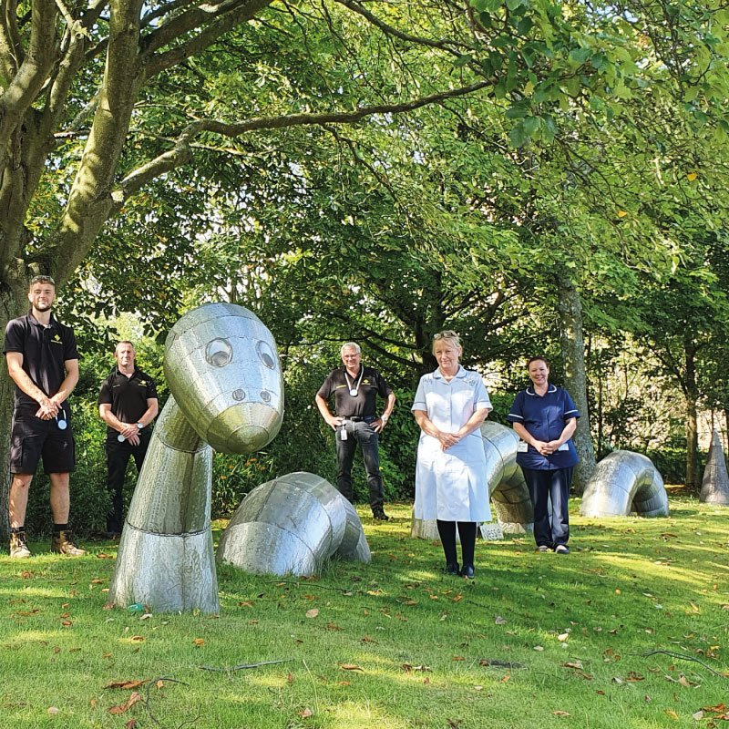 staff from St oswald's and Universal Wolf standing next to Nessie metal installation