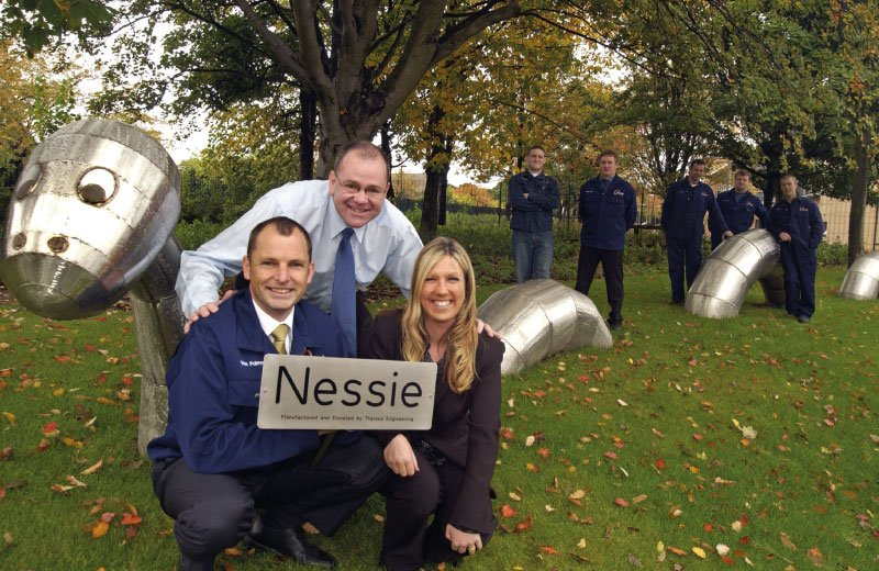 Staff from St Oswald's Hospice and Universal Wolf standing next to Nessie metal installation