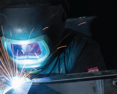 close up of a welder wearing a mask