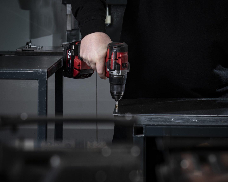 Sheet metal fabricator holding a hand drill